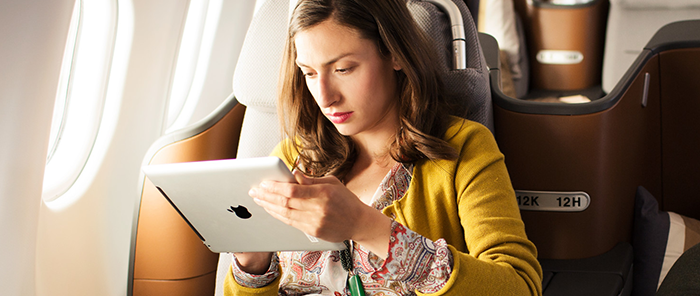 alt= woman uses tablet on board of aircraft