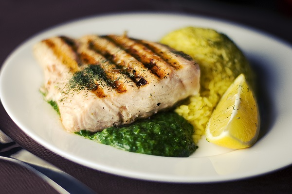 cooked fish on plate with lemons and spinach