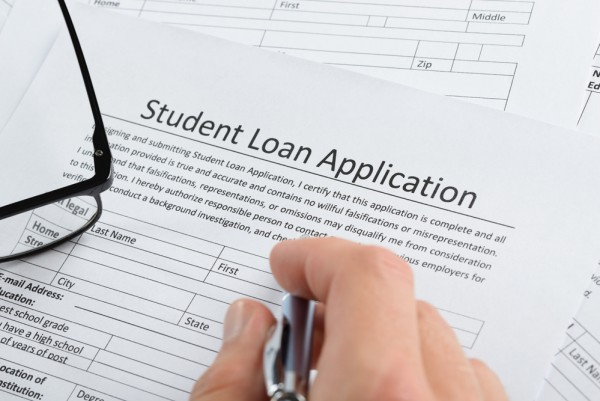 Closeup Of Hand Holding Pen Over Student Loan Application