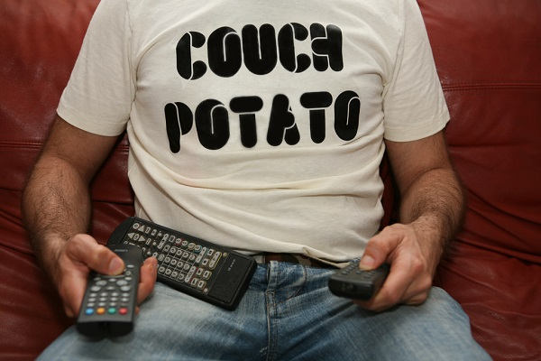 a man with a couch potato shirt sitting with remotes on him and a sedentary lifestyle