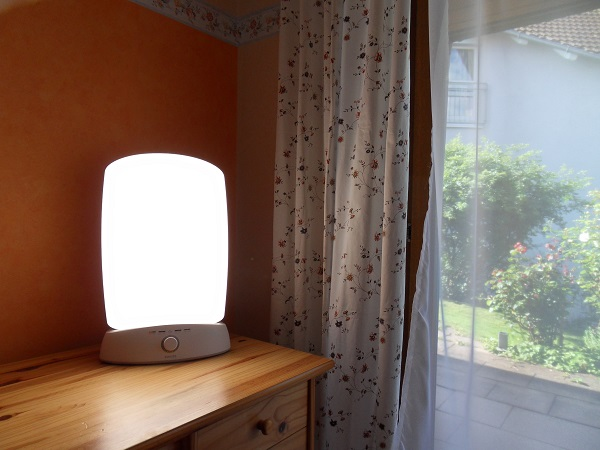 light therapy lamp on a drawer near window