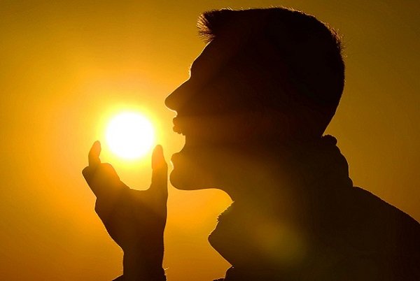 Man posing as he is eating the sun to suggest vitamin D intake.