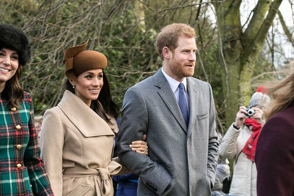 meghan markle holding prince harry's arm with kate middleton to her left
