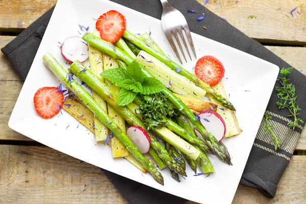 asparagus cooked with other vegetables, mint, and fruits on a plate